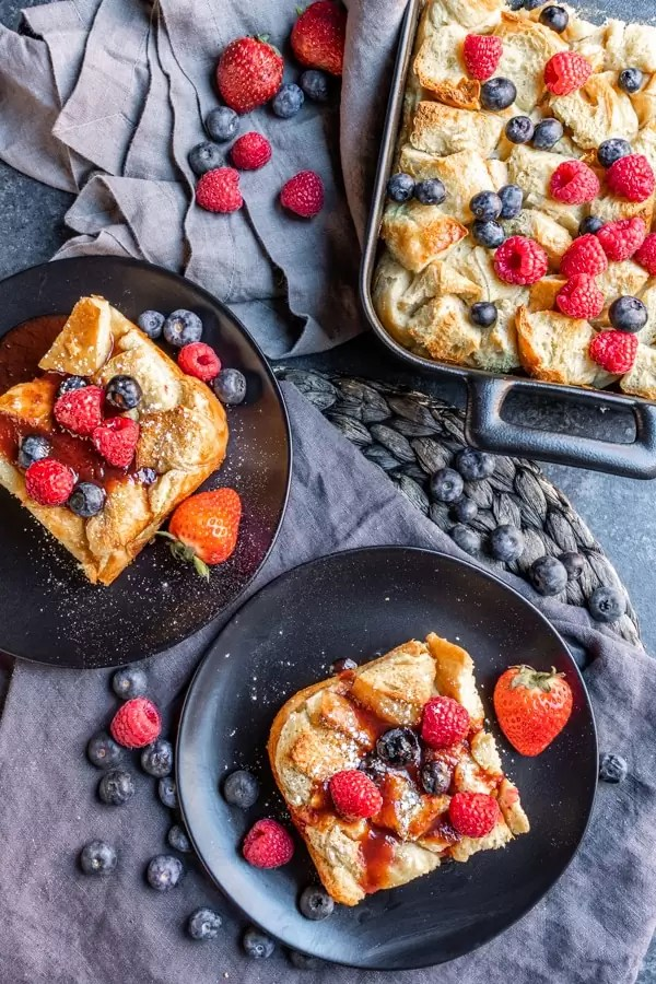 table with Overnight French Toast Bake on plates and platter topped with fresh berries