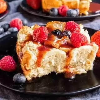 Overnight French Toast Bake on a black plate with fruit syrup and fresh berries