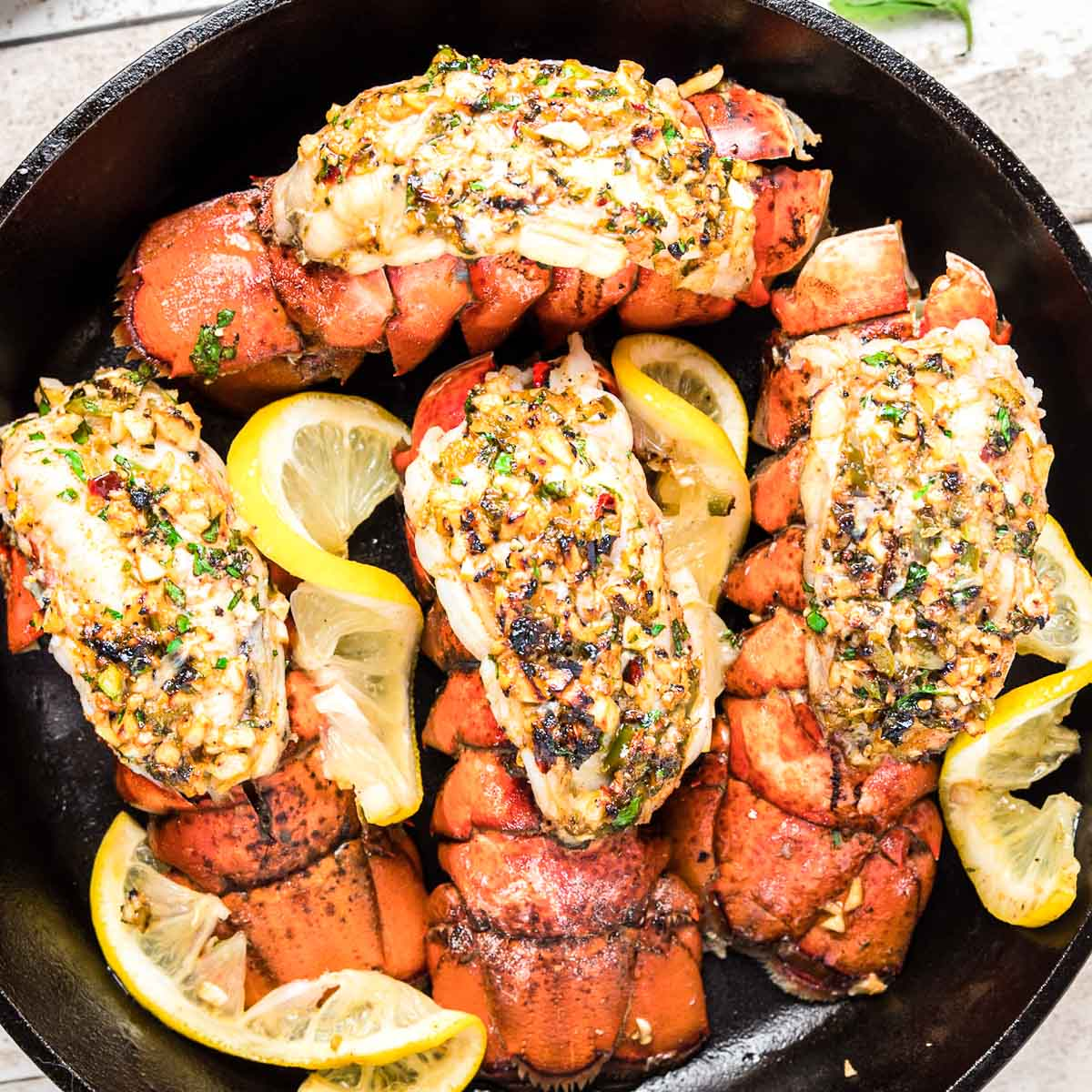 Top down photo of broiled lobster tails in a cast iron skillet