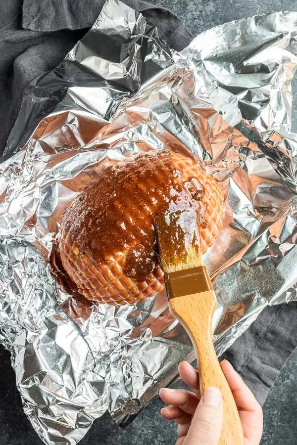 brushing Instant Pot Ham with brown sugar on foil