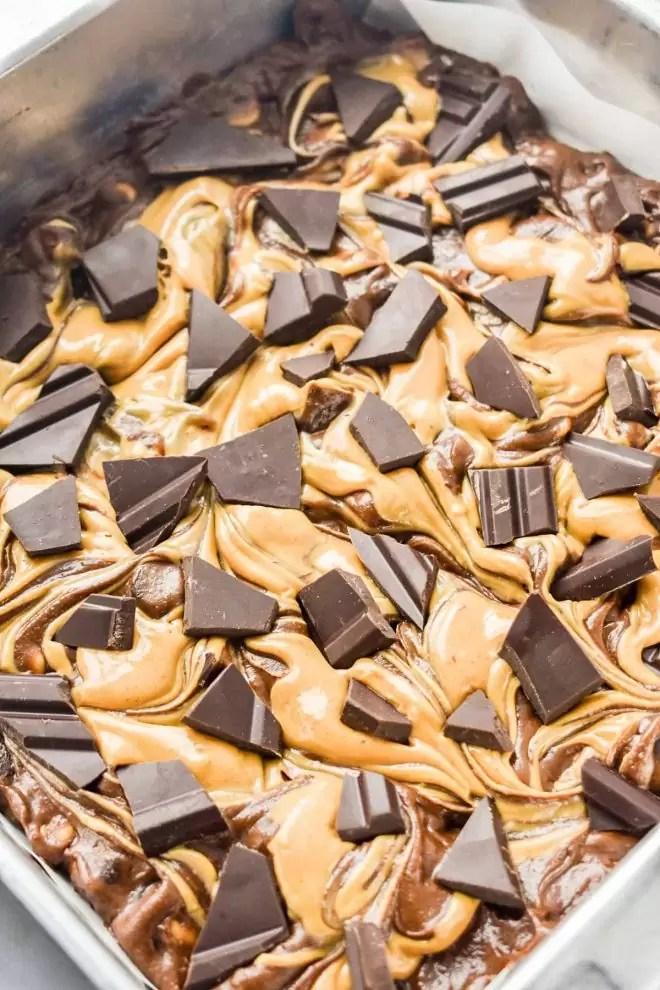 broken pieces of dark chocolate on top of Dark Chocolate Peanut Butter Brownies