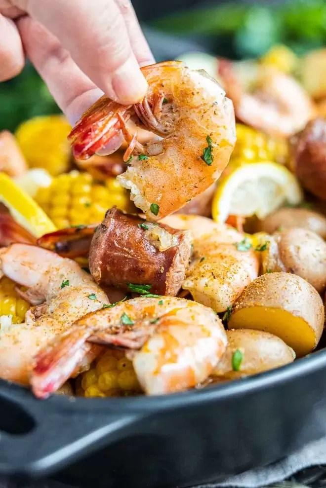 holding a shrimp from ingredients for a Instant Pot Shrimp Boil
