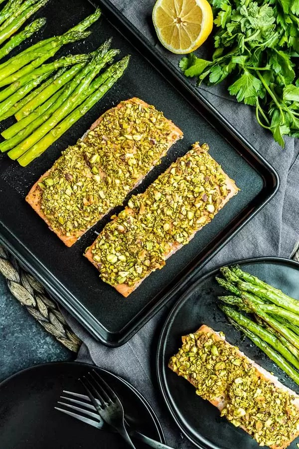 Two pieces of pistachio crusted salmon on a black sheet pan