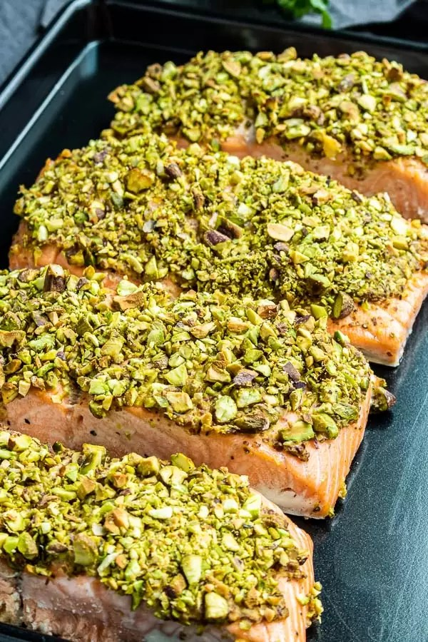 Pistachio crusted salmon filets on a black sheet pan