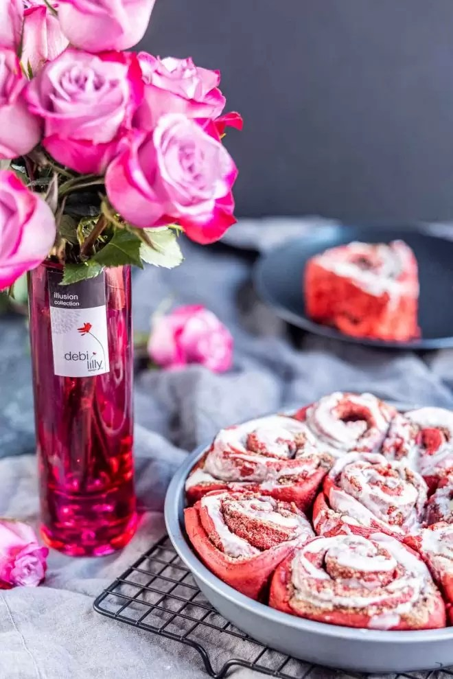 pink roses in a vase with a pan of Red Velvet Cinnamon Rolls
