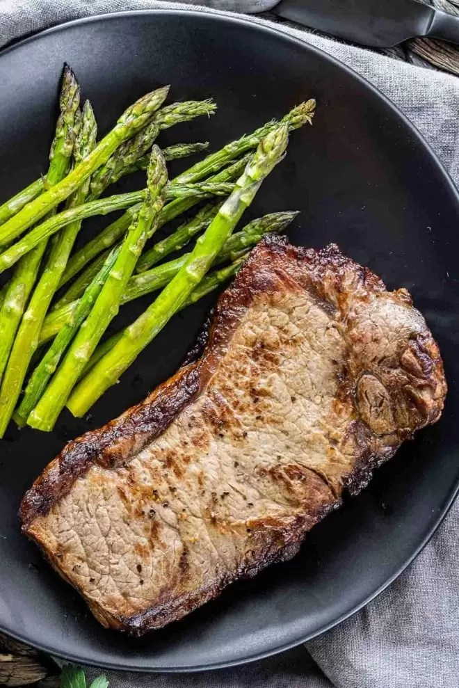 Air Fryer Steak on a plate with asparagus