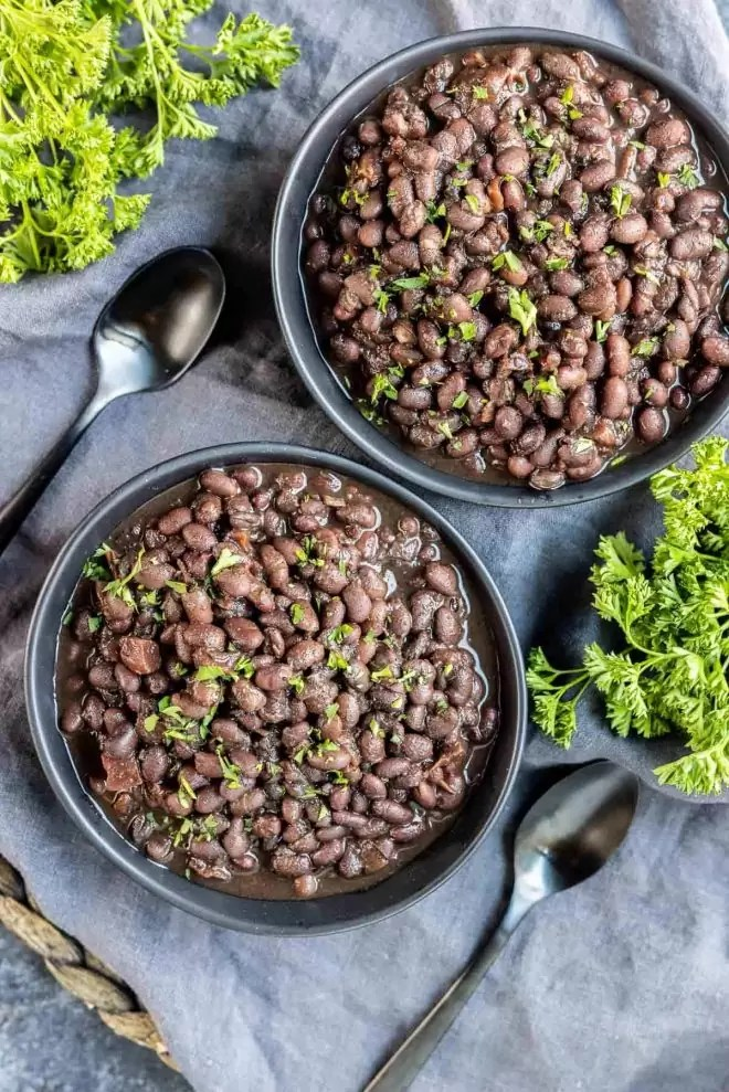 two black bowls of Instant Pot Black Beans