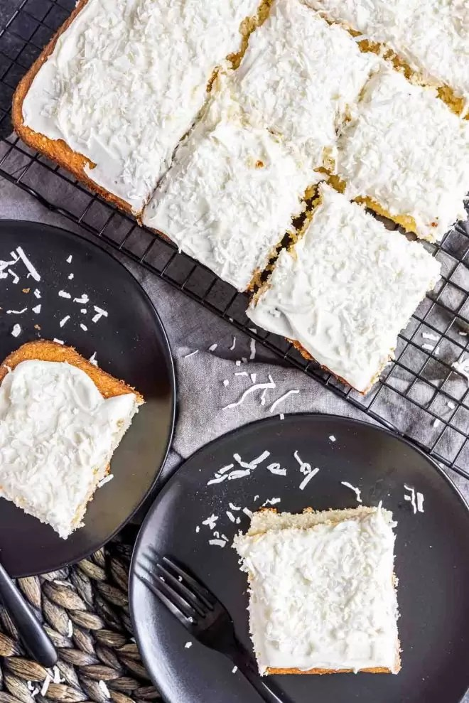 Coconut Sheet Cake cooling on rack with slices on plates