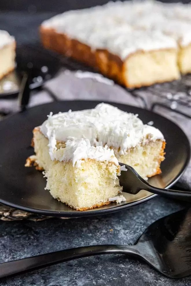 piece of Coconut Sheet Cake on a plate with a fork