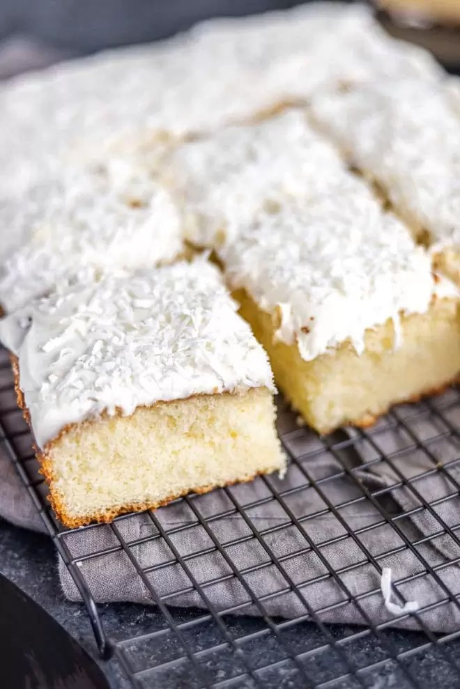 cut Coconut Sheet Cake on cooling rack