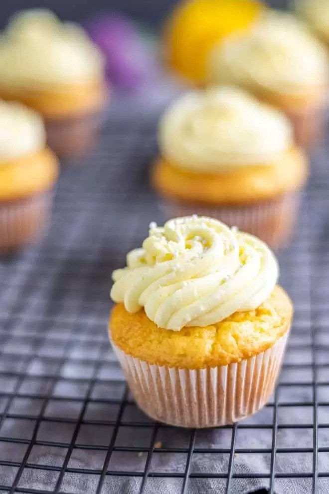 Lemon cupcake topped with a swirl of yellow lemon buttercream and white sprinkles