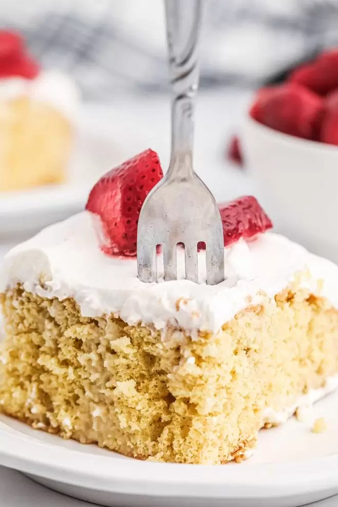 Tres Leches Cake on a plate with a fork in it
