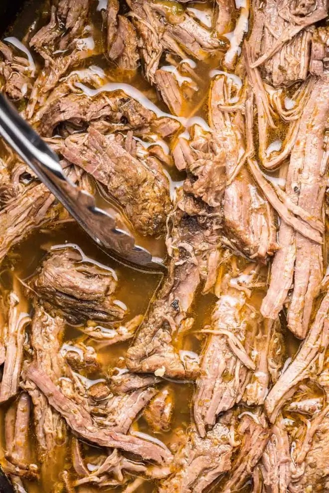 Crock Pot Italian Beef in slow cooker with tongs