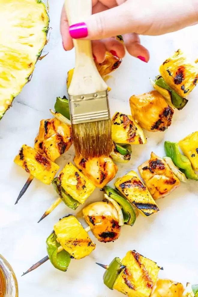 brushing teriyaki sauce on Grilled Teriyaki Chicken and Pineapple skewers