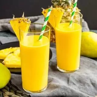 two Mango Pineapple Smoothie with pineapple wedges