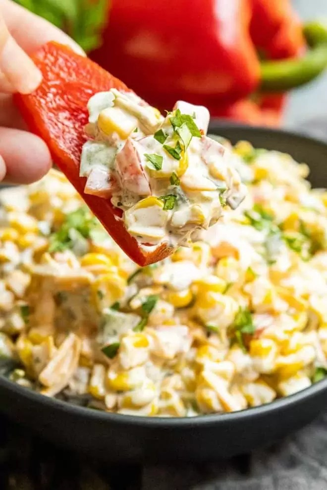 holding a red pepper slice with Creamy Jalapeno Corn Dip