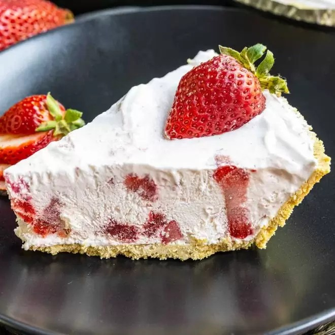 slice of Frozen Strawberry Pie on a black plate with fresh strawberries on top