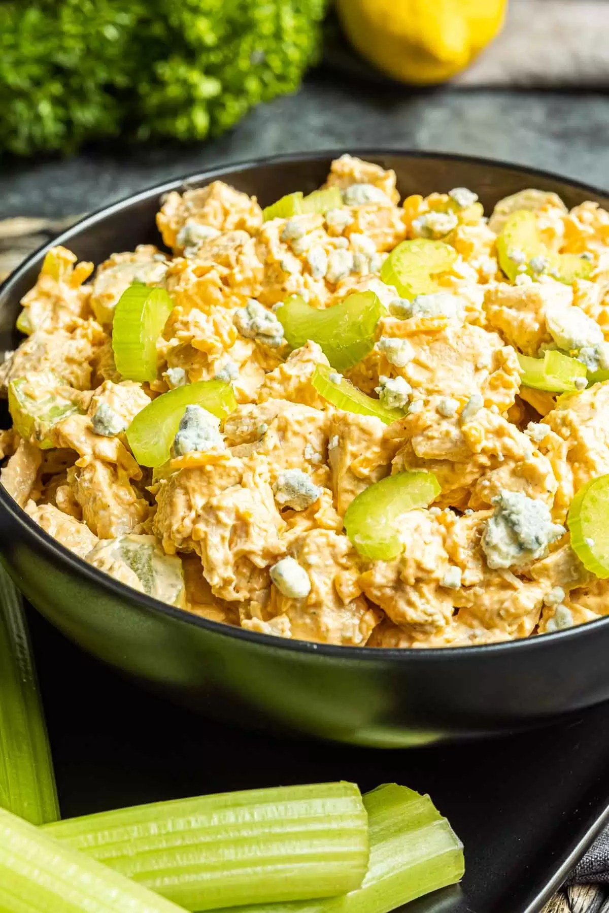 Buffalo Chicken Salad in a black bowl topped with celery