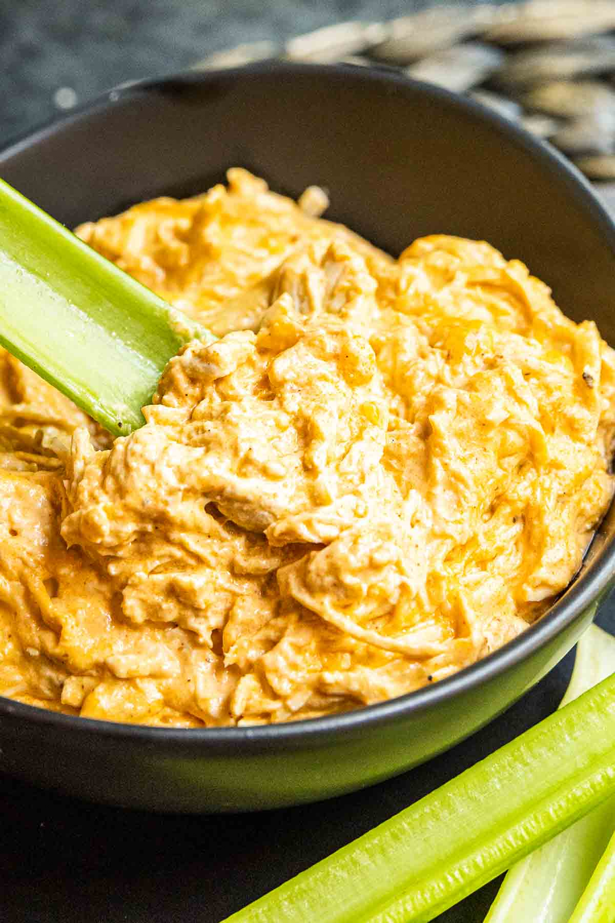 bowl of Instant Pot Buffalo Chicken Dip with celery stick in it