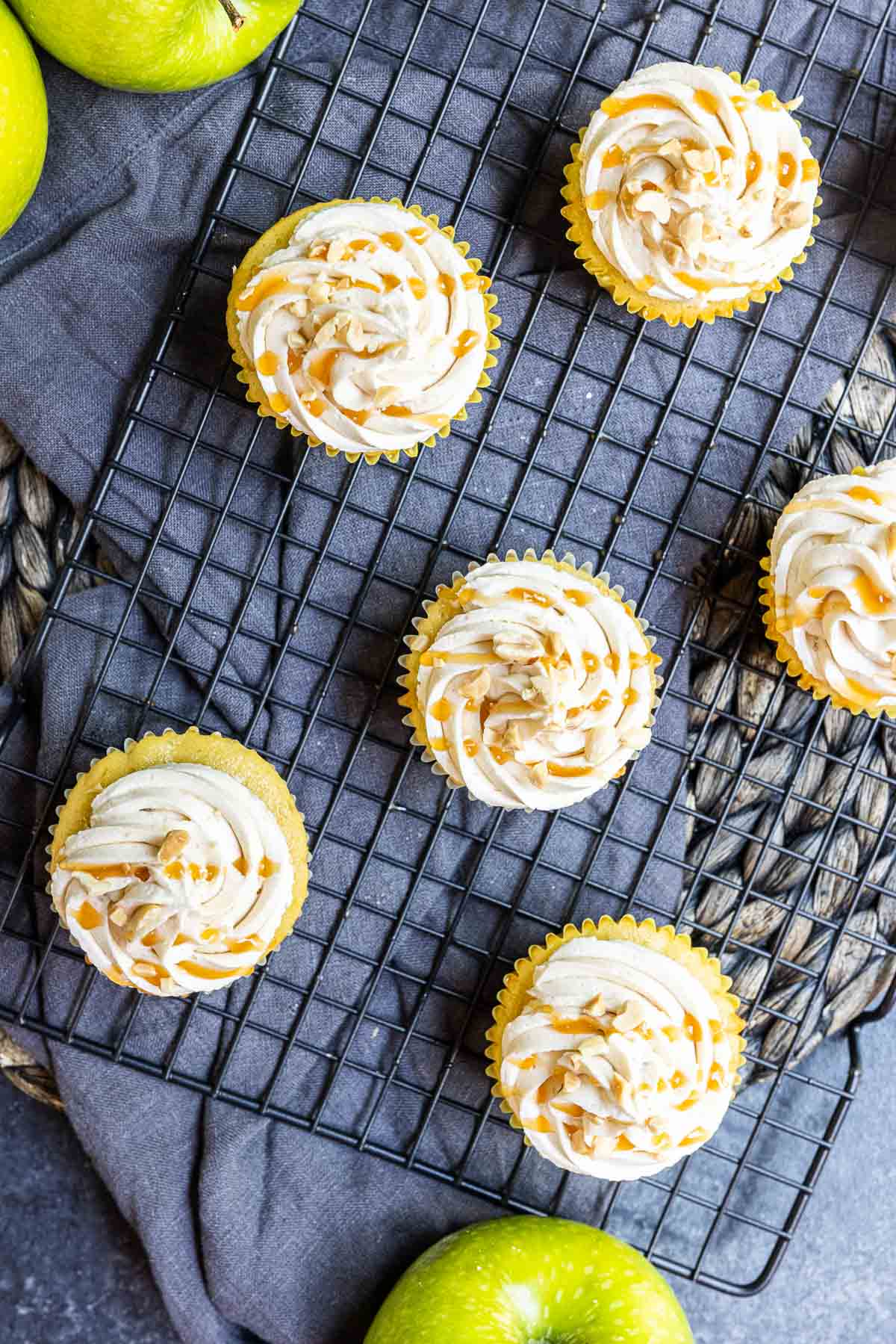 Top down shot of frosted caramel apple cupcakes with a drizzle of caramel on top