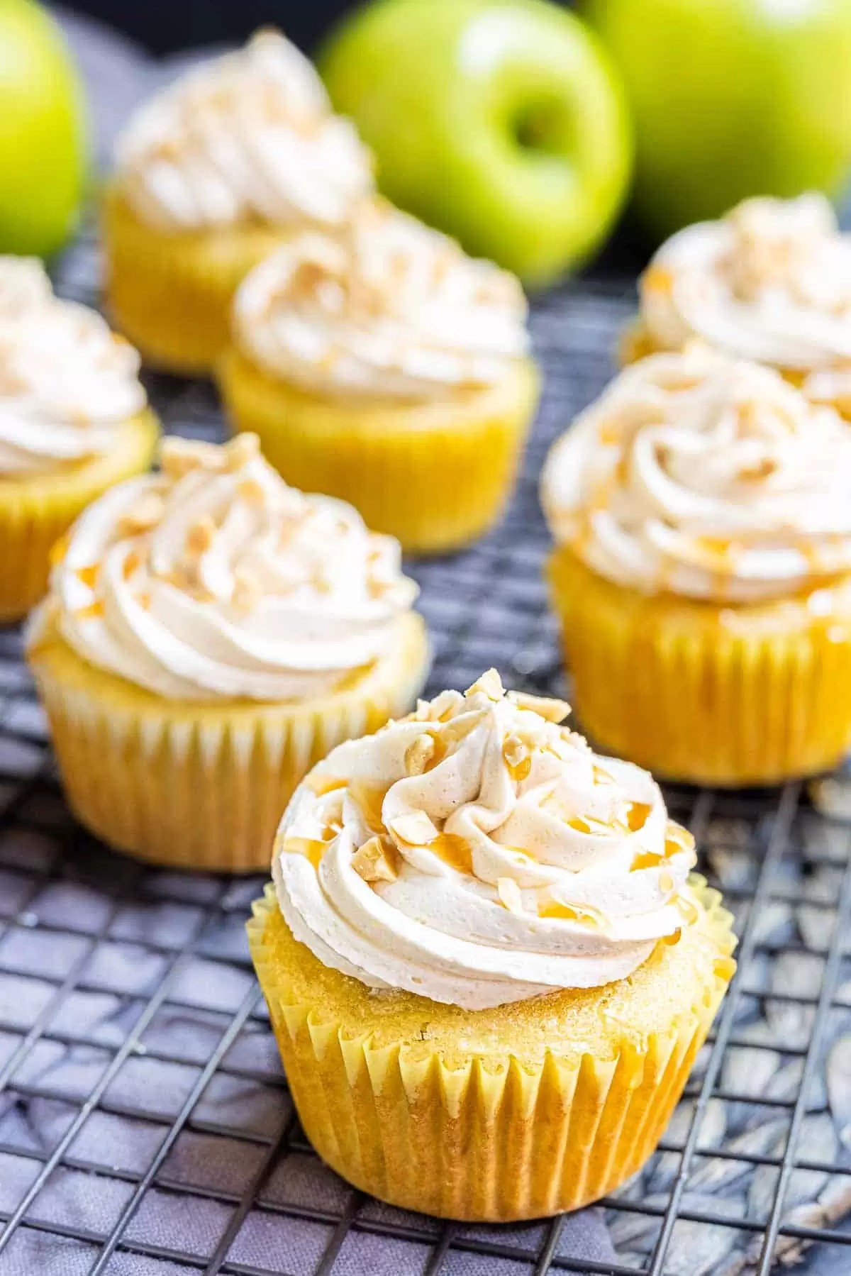 Caramel apple cupcakes with a drizzle of caramel sauce on top.