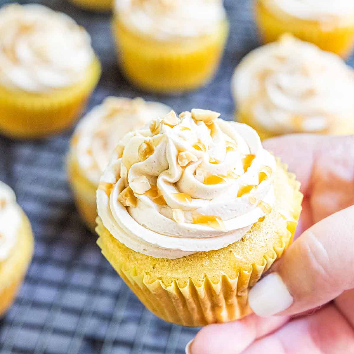 Hand holding frosted caramel apple cupcakes