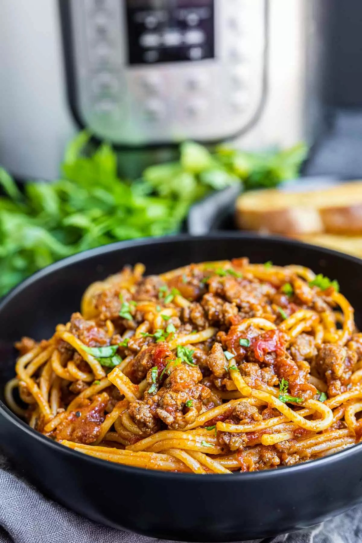 Instant Pot Spaghetti in a black bowl with Instant Pot