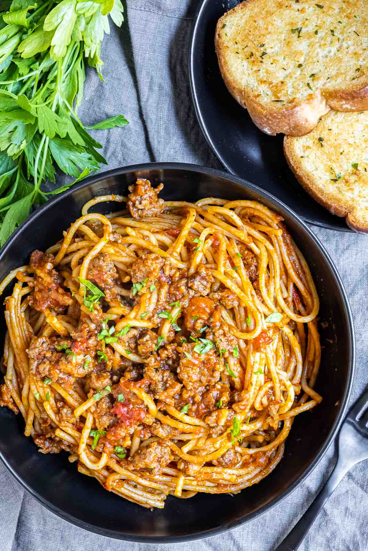 Instant Pot Spaghetti in a black bowl with garlic bread