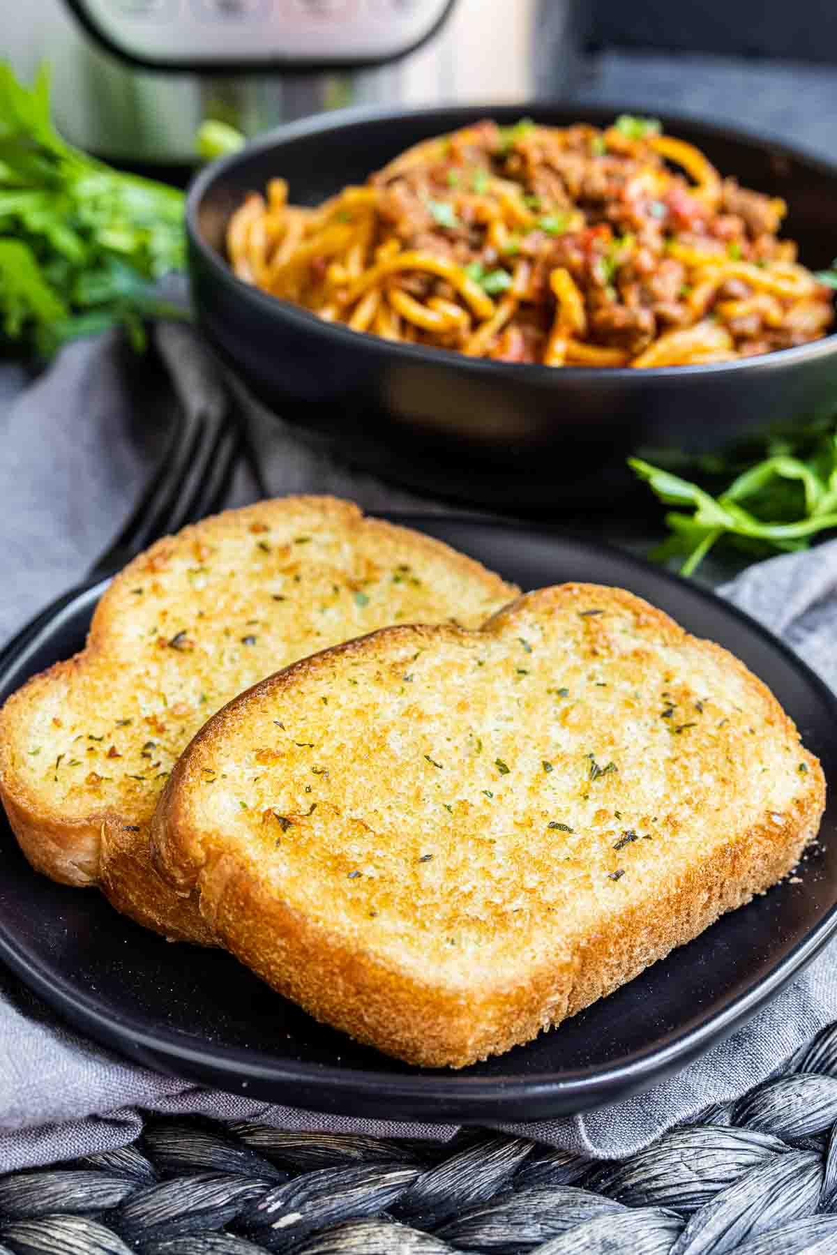 Texas Toast on a plate with spaghetti in a bowl