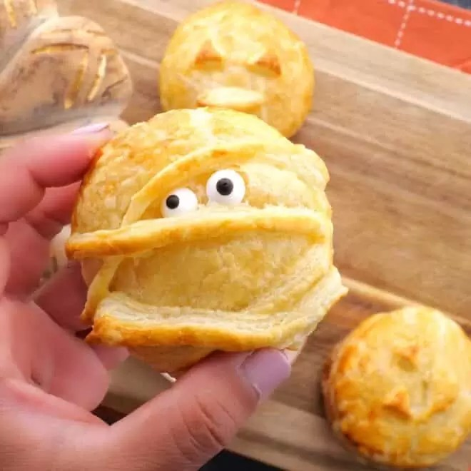 holding Halloween Baked Cheese mummy with eyes