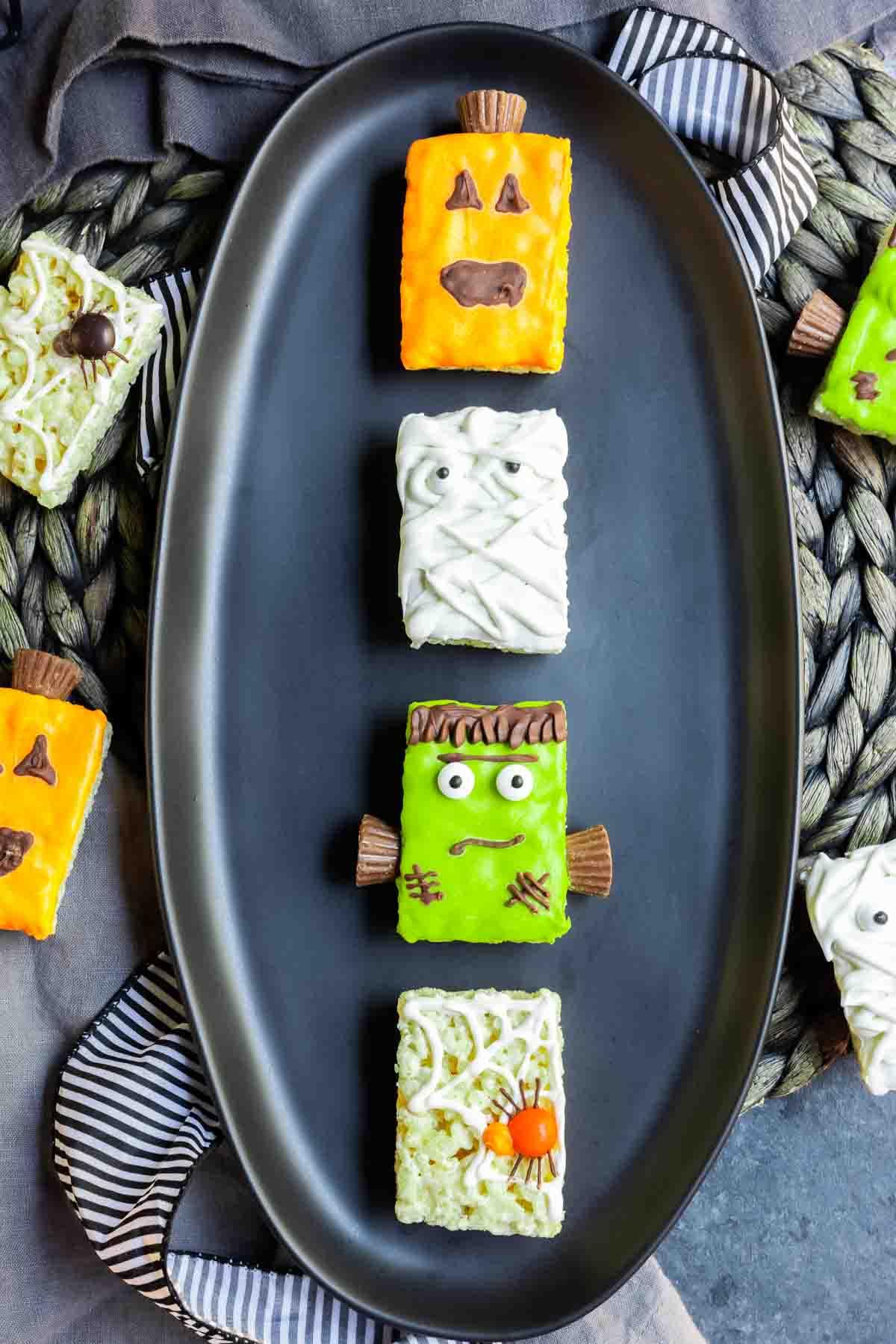 4 Halloween Rice Krispies Treats styles, pumpkin, mummy, Frankenstein, and spider, on a black plate