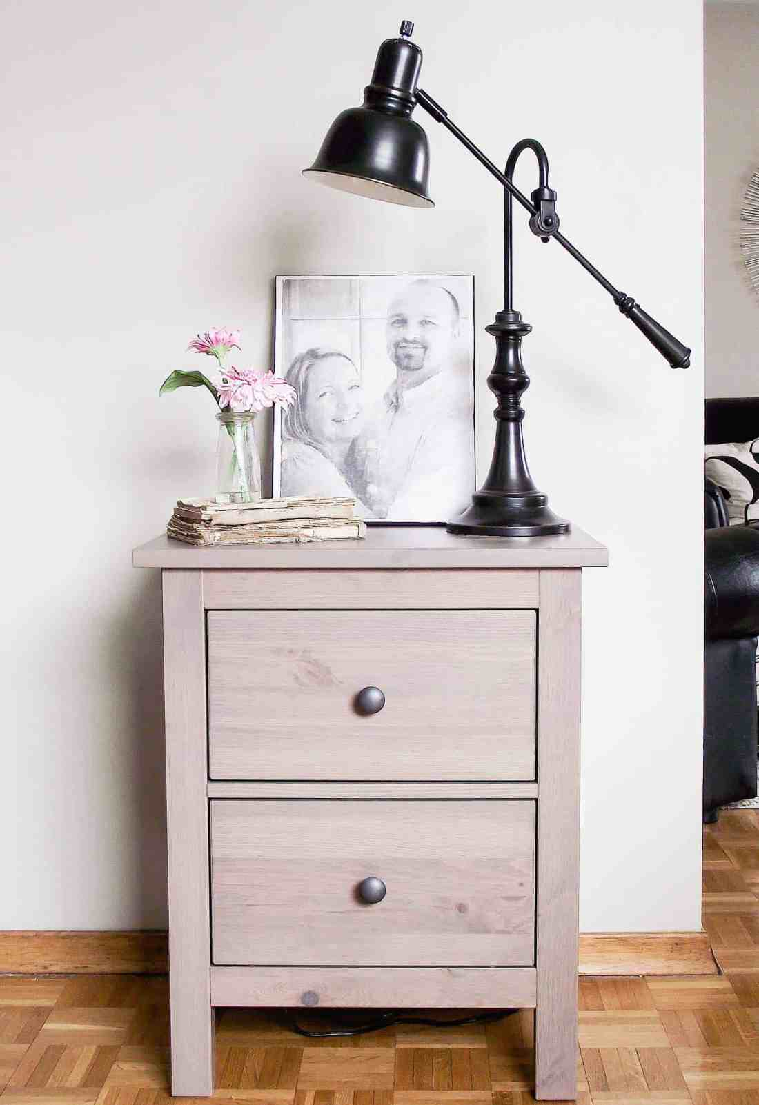 black and white photo on canvas on nightstand with lamp and flowers on stacked books