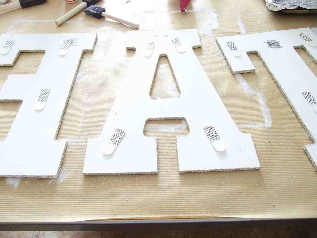 Applying command strips to back of letter for hanging giant glitter EAT sign.