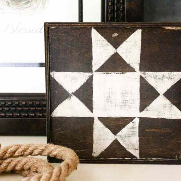 mini barn quilt on a board with rope next to it