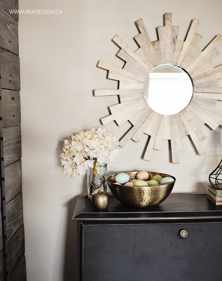 wood starburst mirror on wall above black painted secretary desk holding faux easter eggs in a gold bowl beside a vase of pink flowers