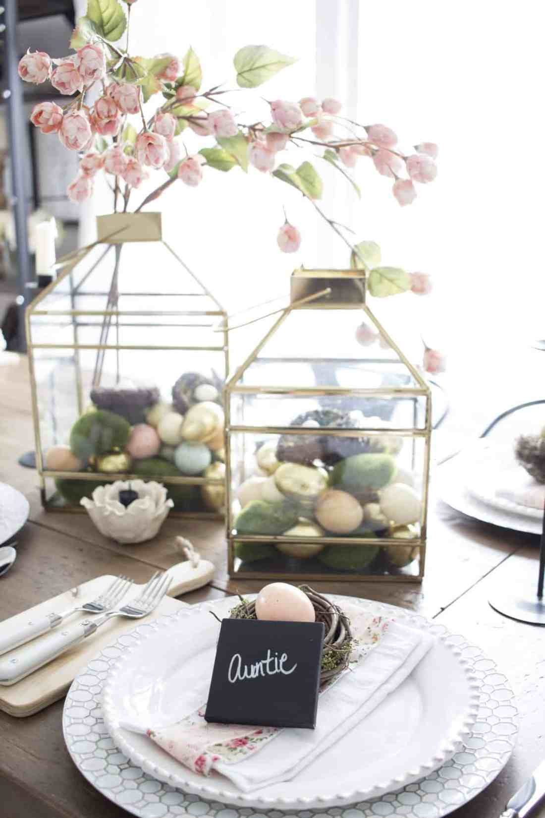 Gold lanterns filled with easter eggs, moss and nests