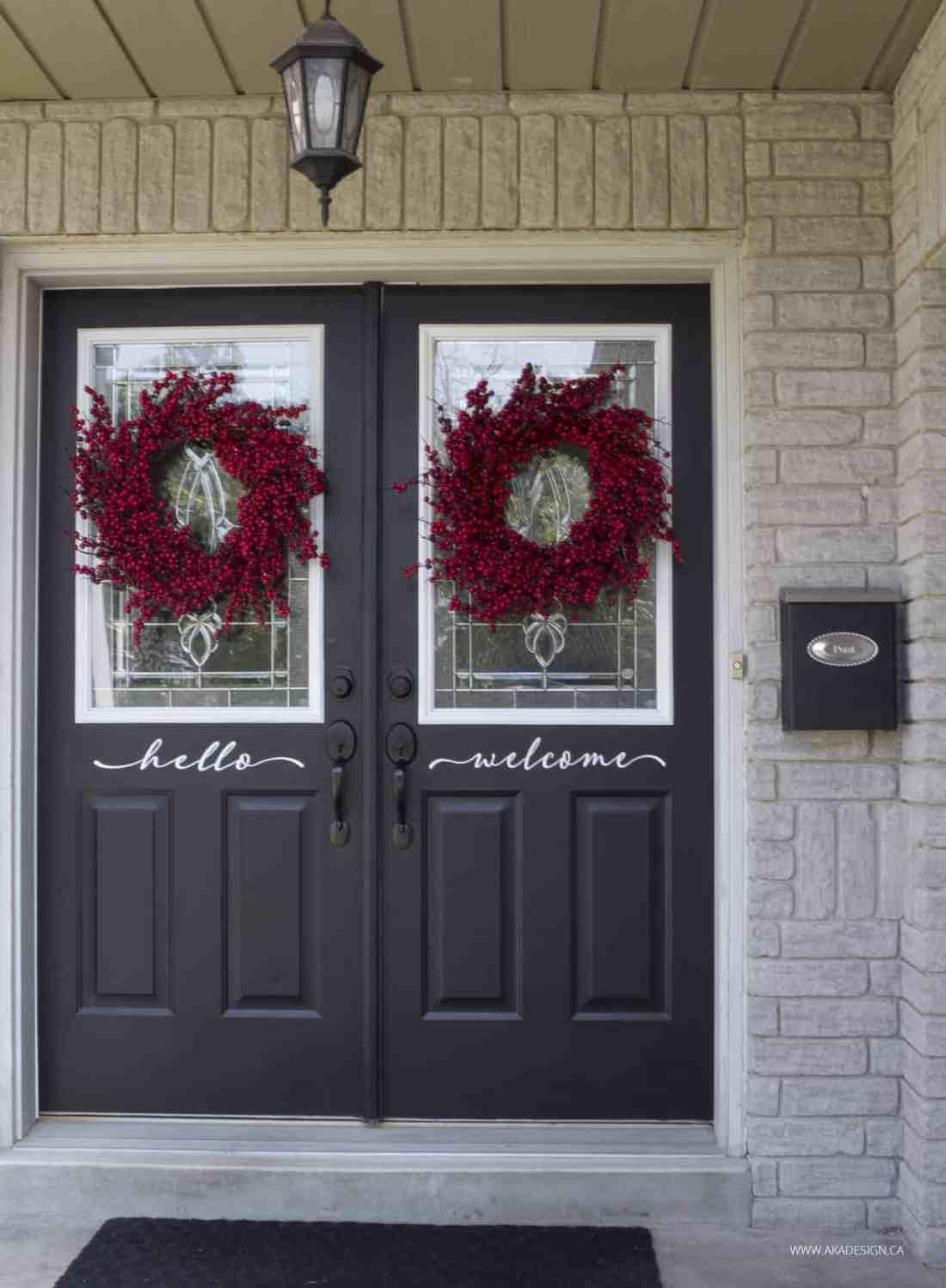 black front doors red berry wreath