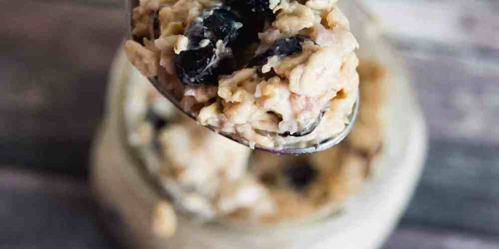 Blueberry Granola Overnight Oatmeal in mason jar on wood table, some on spoon above
