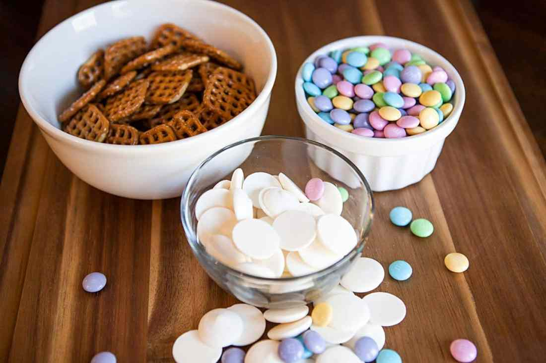 flower pretzel bites ingredients - pretzels, white chocolate melts and pastel m & m's in bowls on wood counter