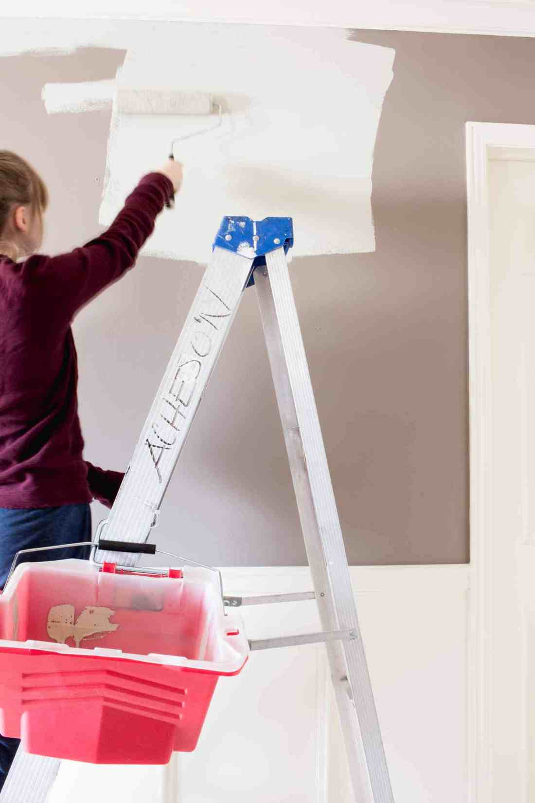 Teenager on ladder painting the wall