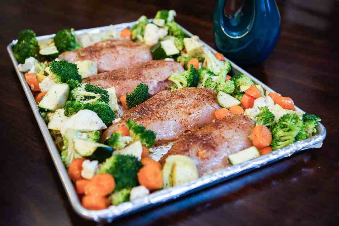 chicken and veggies on pan ready to go into oven