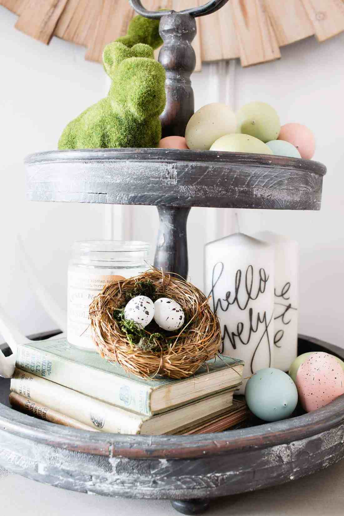 farmhouse tiered tray decorated with moss bunnies, faux pastel colored eggs, nests and books