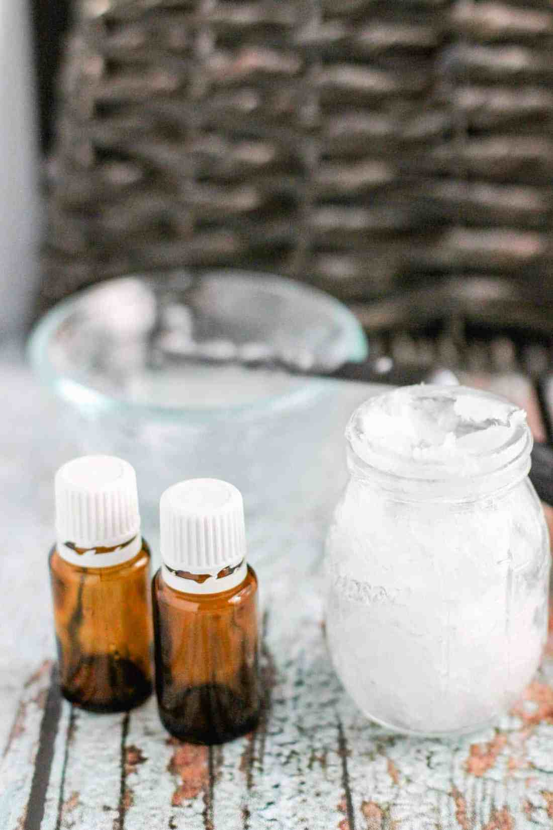 homemade vapour rub in mason jar with essential oil bottles on table