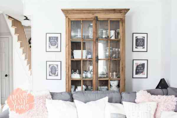 set of four free chalkboard style printables on the wall, two on either side of a pine wood hutch