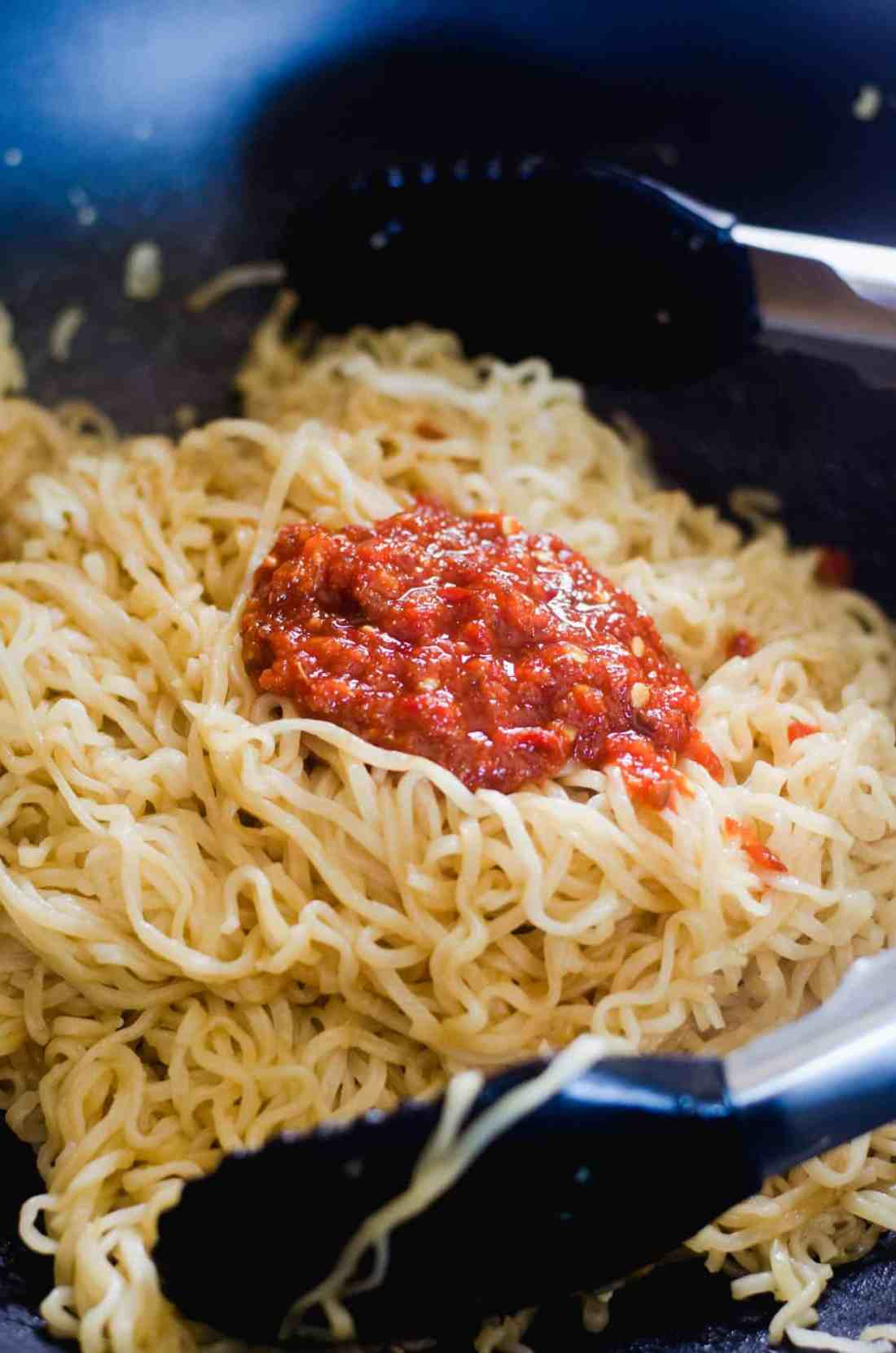 adding chili sauce to Asian noodles in wok