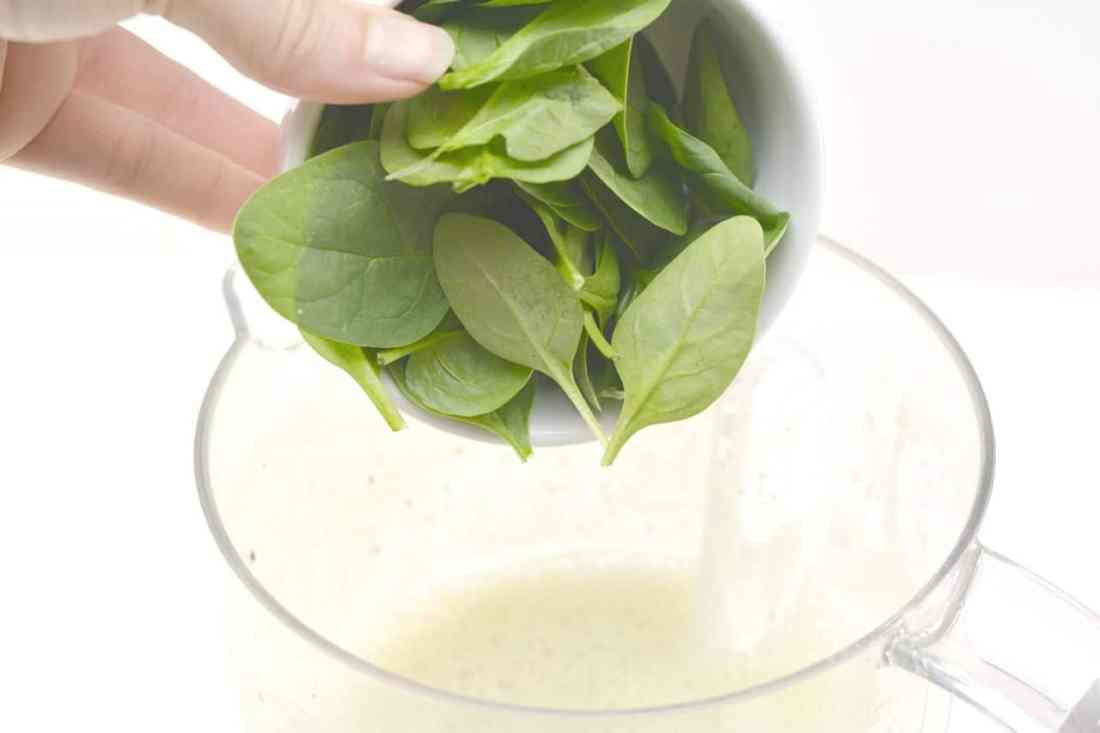 adding spinach to blender