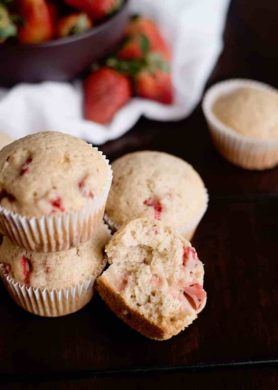 strawberry muffins stacked on a counter, one with a bite out of it.
