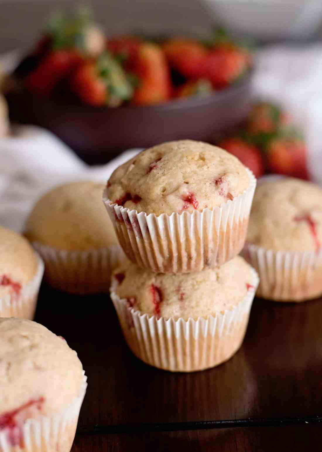 fresh baked strawberry muffins stacked on a dark wood counter