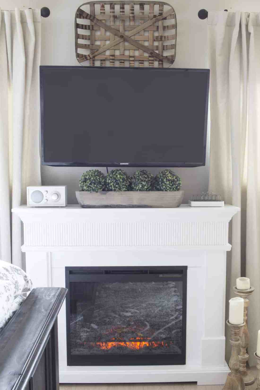 tv over electric fireplace in bedroom