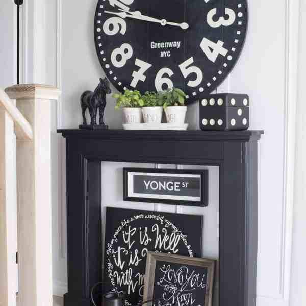 black mantel huge clock signs plants